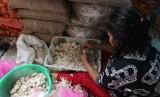 Pedagang mengupas kulit bawang putih di pasar tradisional. ilustrasi