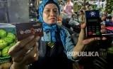 Pedagang menunjukkan kartu e-money dan mesin Q Cash saat peluncuran implementasi pembayaran non tunai di Pasar Mayestik, Jakarta, Rabu (4/4).