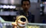 Pegawai menunjukan perhiasan emas di Toko Emas Cantik, Pasar Tebet, Jakarta, Jumat (9/10).