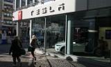 Pejalan kaki melewati gerai mobil Tesla di Jerman.