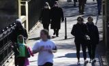 Siswa Muslim Inggris Jadi Korban Termuda Corona. Pejalan kaki mengenakan masker di Regents Park di London, Inggris, Senin (23/3). Pemerintah Inggris mendorong warga jaga jarak satu sama lain untuk menghentikan penyebaran virus corona.