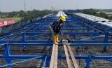 Pekerja beraktivitas di proyek pembangunan konstruksi jalan tol layang Jakarta-Cikampek (Japek) II di Bekasi, Jawa Barat, Jumat (27/7).