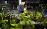 Pekerja membawa tabung gas elpiji tiga kilogram (gas melon) untuk dipindahkan ke truk pengangkut gas di agen penjualan gas, Mampang, Jakarta, Senin (31/10).