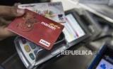 Pekerja menunjukan kartu uang elektronik sebelum isi ulang (top-up) di Bandung, Jawa Barat, Selasa (19/9). Ketua Himpunan Bank-bank Milik Negara (Himbara) Maryono menyatakan sepakat membatalkan rencana pengenaan biaya isi ulang (top-up) uang elektronik menyusul besarnya penolakan dari masyarakat.