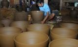 Pekerja menyelesaikan proses pembuatan gerabah guci dari tanah liat. (ilustrasi)