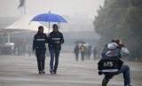 Pembalap Sauber, Antonio Giovinazzi (kedua kiri) berjalan di sirkuit Shanghai yang diguyur hujan, Kamis (6/4). Sesi latihan bebas GP Cina pada hari ini dibatalkan akibat cuaca buruk.