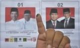 Pemilih menunjukkan jari kelingking usai menggunakan hak pilihnya.