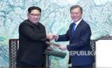Pemimpin Korea Utara Kim Jong Un, kiri, dan Presiden Korea Selatan Moon Jae-in berjabat tangan setelah menandatangani pernyataan bersama di desa perbatasan Panmunjom di Zona Demiliterisasi, Korea Selatan, Jumat (27/4).