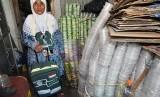 Pemulung Maryani (64 tahun) dengan koper hajinya diantara bekas minuman kemasan plastik yang dikumpulkannya untuk dijual di Kampung Pulo Geulis RT 02/04, Kelurahan Babakan Pasar, Kota Bogor, Jawa Barat, Jum'at (12/7/2019).