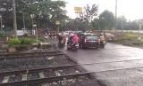 Pengendara melewati palang pintu di pertigaan di samping Stasiun Cakung, Jakarta Timur