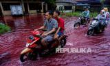 Pengendara motor melintas di jalan perkampungan yang tergenang banjir berwarna merah di Jenggot, Pekalongan, Jawa Tengah, Sabtu (6/2/2021). Menurut warga setempat, air banjir berwarna merah itu disebabkan oleh pencemaran limbah pewarna batik berwarna merah karena di lokasi tersebut terdapat ratusan pelaku usaha batik.