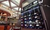 Pengunjung melintasi layar elektronik pergerakan saham di Bursa Efek Indonesia, Jakarta.