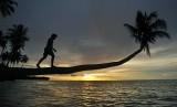 Pengunjung menikmati matahari terbenam di Pantai Mapadegat, Mentawai, Sumatra Barat.