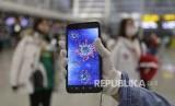 Penumpang menunjukkan gambar ilustrasi coronavirus pada ponselnya di  Bandara Guangzhou, Provinsi Guangdong, China, Kamis (23/1).  Wabah Virus Wuhan di China telah memakan korban 17 orang meninggal dan ratusan lainnya positif terjangkit.