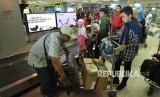 Penumpang pesawat udara mengemasi barang bagasi mereka setibanya di Bandara Internasional Minangkabau (BIM), Padangpariaman, Sumatra Barat, Kamis (7/6).