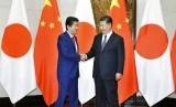 Perdana Menteri Jepang Shinzo Abe (kiri) berjabat tangan dengan Presiden Cina Xi Jinping di Diaoyutai State Guesthouse di Beijing, Cina, Jumat (26/10).