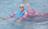 Perempuan berenang mengenakan baju renang tertutup.