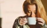 Perempuan meminum secangkir kopi.