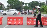Personel kepolisian berjaga di perbatasan Medan-Tanjung Morawa Kabupaten Deliserdang, Sumatera Utara, Ahad (26/4/2020). Polda Sumut melakukan penyekatan atau pembatasan mobilitas jalan pintu masuk ke Kota Medan untuk mencegah gelombang arus mudik Lebaran di tengah pandemi COVID-19.