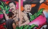 Peserta menggambar mural saat mengikuti Lomba Mural Shelter Airbrush di Kestalan, Banjarsari, Solo, Jawa Tengah, Rabu (4/12/2019). Lomba mural yang diikuti 19 peserta tersebut untuk memperindah dan mempercantik pusat kawasan pengecatan airbrush agar dapat menarik turis.