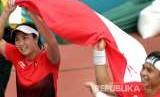 Petenis Indonesia Christopher Benjamin Rungkat (kanan) yang berpasangan dengan Aldila Sutjiadi (kiri) membawa bendera setelah menjadi juara dengan mengalahkan lawannya petenis Thailand Luksika Kumkhum dan Sonchat Ratiwatana pada babak final tenis ganda campuran Asian Games 2018 di JSC Tennis Courts, Palembang, Sumatera Selatan, Sabtu (25/8).
