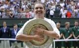 Petenis Rumania, Simona Halep memeluk trofi Wimbledon setelah mengalahkan Serena Williams pada laga final, Sabtu (13/7).