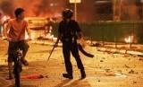 Dua Tewas dalam Kerusuhan di India Akibat Hina Rasulullah. Foto ilustrasi: Petugas antihuru-hara menghalau seorang warga yang melintas di kawasan Little India, Singapura, yang dilanda kerusuhan pada Ahad (8/12/2013)