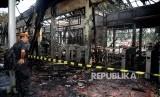 Petugas berjaga di depan bangunan yang hangus terbakar di Stasiun Klender, Jakarta, Jumat (19/5).