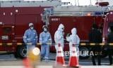 Petugas berpakaian pelindung berdiri di dekat kapal pesiar Diamond Princess berlabuh di Pelabuhan Yokohama untuk mengisi perbekalan di Yokohama, Jepang, Kamis (6/2).  Petugas kesehatan mengkonfirmasi 10 kasus baru positif virus corona selain temuan 10 kasus Rabu kemarin.