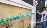 Petugas berpakaian sipil memasang garis larangan melintas di rumah yang diduga menjadi pabrik pembuataan pil jenis Paracetamol Caffein Carisoprodol (PCC) saat penggerebekan oleh Badan Narkotika Nasional (BNN), di Jalan Raya Halmahera, Semarang, Jawa Tengah, Ahad (3/12).