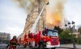 Petugas dari Paris Fire Brigade berusaha memadamkan api di Katedral Notre-Dame, Selasa (16/4). Gereja bersejarah berusia hampir 900 tahun itu terbakar pada Senin (15/4).