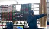 Petugas dengan pakaian pelindung bekerja di depan layar yang menunjukkan pergerakan saham di Shanghai Stock Exchange, Shanghai, China, Jumat (14/2). Saham-saham China menghapus kerugian awal menjadi ditutup lebih tinggi pada perdagangan Jumat (21/2).