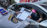 Petugas Dishub DKI memeriksa surat izin keluar masuk (SIKM) yang dibawa pengendara sebagai syarat masuk wilayah Jakarta.