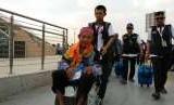 Petugas Haji Daker Bandara menuntun jamaah Kloter 63 Debarkasi Jakarta-Bekasi menuju paviliun Bandara Amir Muhammad bin Abdulaziz, Madinah, Selasa (25/9). Kloter tersebut merupakan kloter terakhir yang dipulangkan ke Tanah Air pada musim haji tahun ini.