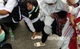 Petugas haji Indonesia memakaikan sandal pada jamaah yang kehilangan di Gerbang 21 Masjid Nabawi, Jumat (27/7). Tim kesehatan membagikan ribuan sandal mengingat berbahayanya berjalan-jalan tanpa sandal di tengah cuaca panas Madinah.