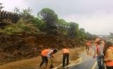 Petugas jasa marga sedang membersihkan tanah bekas longsoran di tol Cipularang. Longsor di Tol Cipularang terjadi akibat curah hujan tinggi guyur Kampung Hegarmanah, Bandung