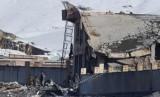 Petugas keamanan Afghanistan memeriksa gedung yang roboh pacsaserangan yang dilakuksan Taliban dan menyebabkan lebih dari 100 orang tewas.