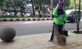 Petugas kebersihan sedang membersihkan trotoar di salah satu sudut Kota Bandung.