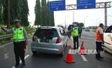 Petugas kepolisian bersama petugas Jasa Marga menghalau pengendara berpelat nomor ganjil yang akan memasuki tol Jakarta - Tangerang (Janger) saat dimulainya hari pertama uji coba penerapan sistem ganjil genap di Gerbang Tol Tangerang 2, Tangerang, Banten, Senin (16/4).