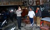 Petugas kepolisian membubarkan warga yang berkumpul di salah satu waruNg kopi