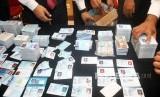 Petugas kepolisian merapikan barang bukti KTP elektronik yang tercecer / Ilustrasi