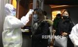 Petugas kesehatan mengenakan pakaian anti bahan berbahaya (hazardous material suit) memerilksa suhu tubuh penumpang yang datang dari daerah Wuhan di  Bandara Beijing, China.  Wabah Virus Wuhan di China telah memakan korban 17 orang meninggal dan ratusan lainnya positif terjangkit.