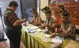 Petugas KPPS membantu warga yang akan memberikan hak suaranya di TPS 005 Pemilu 2019 di Kelurahan Cibadak, Kecamatan Astanaanyar, Kota Bandung, Rabu (17/4).