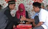 Petugas memandu akad nikah sepasang mempelai di Kantor Urusan Agama (KUA) Kecamatan Palu Selatan, Palu, Sulawesi Tengah, Kamis (22/12).