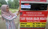 Petugas memasang pengumuman tanda ditutupnya objek wisata Pantai Air Manis, di Padang, Sumatera Barat, Jumat (20/3/2020).