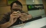 Petugas menaksir emas milik nasabah di Kantor Pusat Pegadaian, Jakarta, Kamis (7/6).
