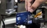 Petugas menarik sebuah kartu kredit pada proses pembuatan kartu kredit BRi