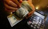 Petugas menghitung uang pecahan dolar Amerika Serikat di gerai penukaran mata uang asing di Jakarta (ilustrasi)
