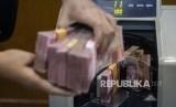 Petugas mengitung uang rupiah di salah satu gerai penukaran uang asing di Jakarta, Rabu (27/11). Dolar AS melemah karena ekspektasi meningkat bahwa Federal Reserve (Fed) akan memangkas suku bunga tahun ini untuk mengurangi tekanan pada ekonomi yang disebabkan oleh virus corona.
