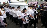 Petugas mengusung peti jenazah anggota KPU Yakuhimo, Papua almarhum Hendry Jovinski saat proses pemakaman di Rewulu Wetan, Sidokarto, Godean, Sleman, Yogyakarta.